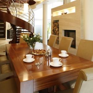 Właściciele lubią przyjmować gości, stąd duży drewniany stół wykonany z drewna merbau, a do kompletu aż osiem krzeseł w przyjemnej miękkiej tapicerce z naturalnej skóry. Fot. Marcin Onufryjuk.