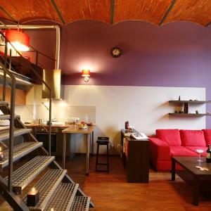 Łagodny charakter aranżacji loftu to efekt zastosowanych kolorów: fioletu i pomarańczu na ścianach oraz czerwieni (kanapa Wajnert, abażury kinkietów i lamp wiszących Massive), które oswajają to industrialne wnętrze. Fot. Marcin Onufryjuk.