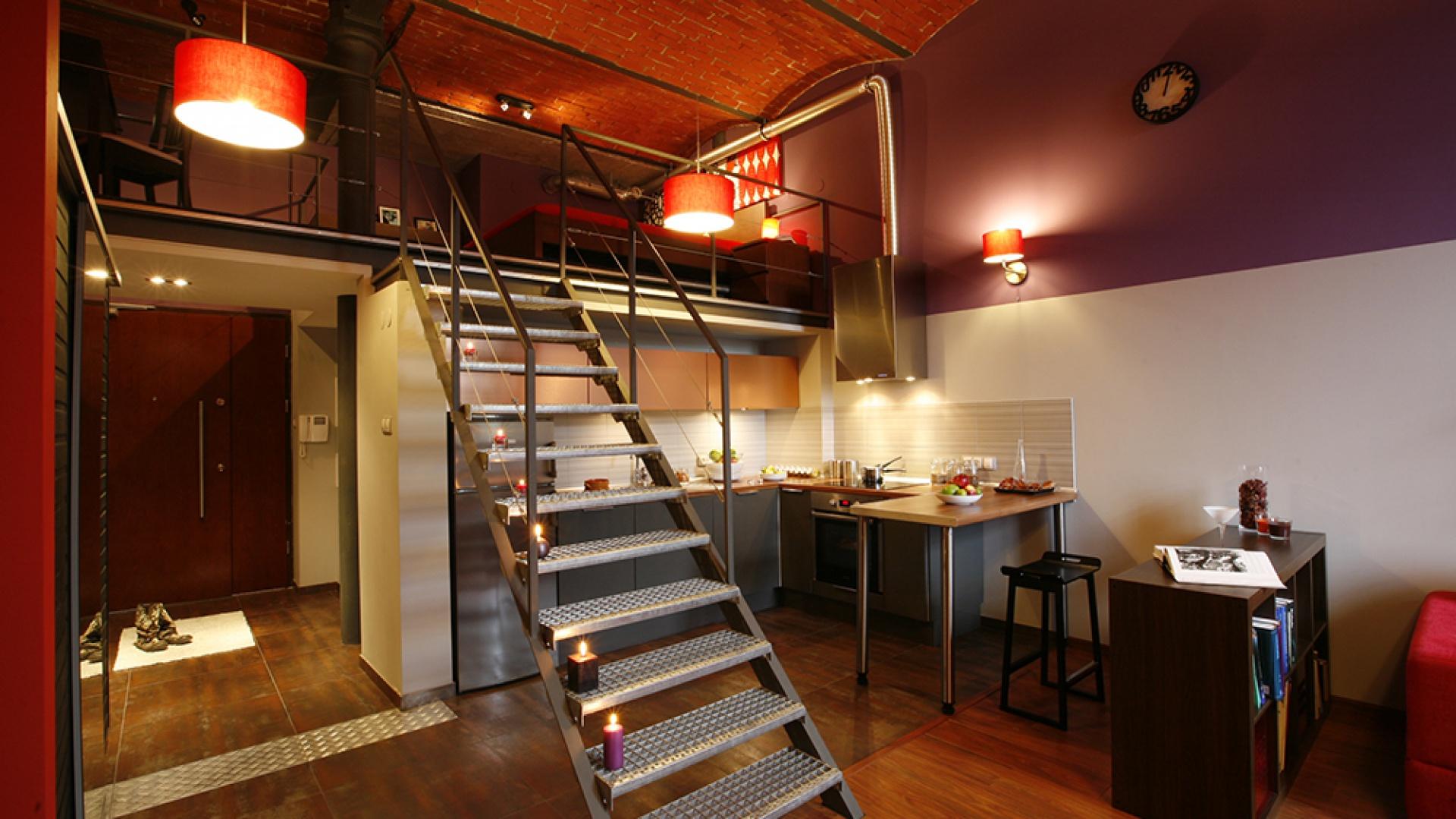 Stalowy kolor frontów szafek dolnych (MDF) tworzy doskonałe tło dla surowej konstrukcji stalowych schodów prowadzących na antresolę. Fot. Marcin Onufryjuk.