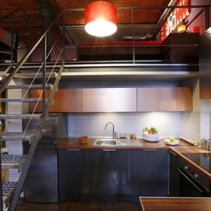 Górną linię zabudowy kuchennej tworzą niskie szafki z frontami w kolorze szczotkowanej miedzi, dolne fronty - w kolorze stali. Fot. Marcin Onufryjuk.