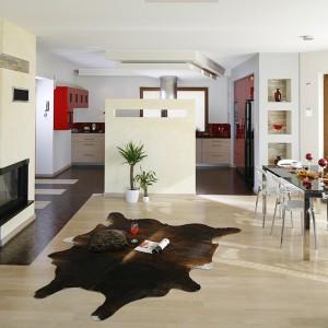 Strefy robocze kuchni pozostają ukryte za ścianką działową. Jej efektowne wykończenie to tynk typu  trawertyn, widoczny również na obudowie kominka. Fot. Bartosz Jarosz.