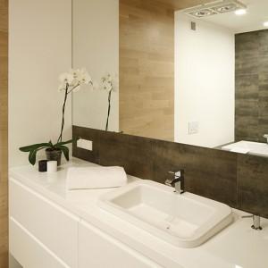W łazience na półpiętrze zastosowano czysty i klarowny podział funkcji - lustro pomnaża harmonię tej przestrzeni. Fot. Bartosz Jarosz.