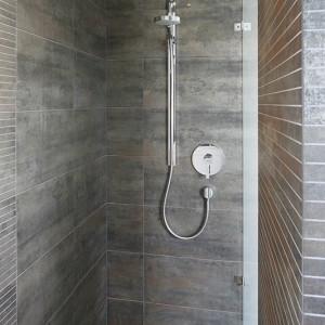 Dla intymności i poczucia kontrolowanej przestrzeni podczas kąpieli ściany prysznica wyłożono hiszpańskimi płytkami w ziemistym kolorze, a z prawej strony wstawiono fragment szklanej tafli. Fot. Bartosz Jarosz.