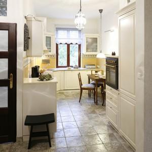 Wnętrze ma charakter zamknięty, jednak nie jest oddzielone drzwiami. Zarówno w kuchni, jak i w korytarzu, zastosowano ten sam materiał podłogowy – płytki gresowe o strukturze przypominającej kamień. Fot. Bartosz Jarosz.