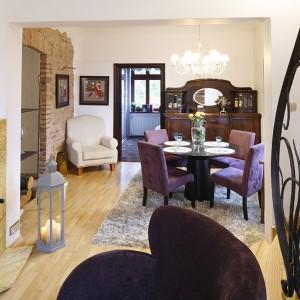 Formalna jadalnia znajduje się w salonie. W bezpośrednim sąsiedztwie starego, dębowego kredensu znalazł się okrągły stół na masywnej podstawie (Bo Concept) oraz tapicerowane fotele w kolorze fuksji (Almi Décor). Fot. Bartosz Jarosz.