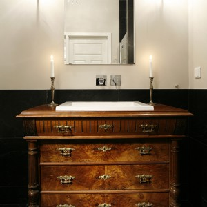 Stylowy charakter wnętrza buduje eklektyczna komoda z XIX wieku, która została dostosowana do instalacji nowoczesnej umywalki. We wnętrzu jest więcej tego typu zestawień. Fot. Bartosz Jarosz.