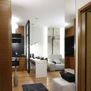 Kuchnia i salon mają charakter połączonej strefy dziennej, co podkreśla zastosowanie tego samego materiału podłogowego. W rezultacie wnętrze stanowi zgraną całość – idealne mieszkanie dla singla. Fot. Bartosz Jarosz.