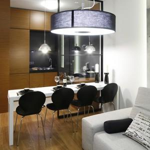 Przy dosyć nietypowym, wąskim stole można usiąść jak przy barze. Wykonany z lakierowanego MDF-u w kolorze złamanej bieli, stanowi wyjątkowy komplet jadalniany z czarnymi krzesłami (Duka). Fot. Bartosz Jarosz.