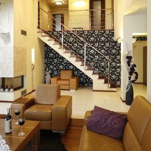 Sofa i fotele kuszą kolorem toffi i obietnicą komfortowego wypoczynku. Grafitowa tapeta ze srebrnym wzorem przyciąga wzrok. Fot. Bartosz Jarosz.