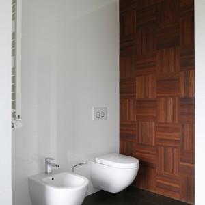 Zastosowanie drewna ociepla wizerunek wnętrza. Na ścianie: mozaika przemysłowa merbau olejowana, w układzie mozaikowym. Ceramika sanitarna z oferty Villeroy