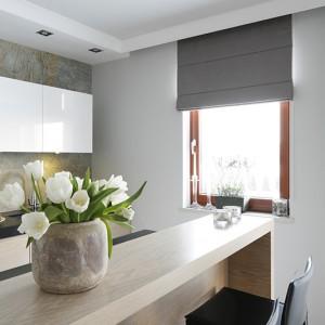 Bielony dąb pojawia się również wpostaci fornirowanych frontów kuchennych iniewielkiej wyspy kuchennej. Wpołączeniu zbielą górnych szafek ikamienną powierzchnią ściany stanowi harmonijne nawiązanie do pozostałych komponentów wnętrza. Fot. Bartosz Jarosz.