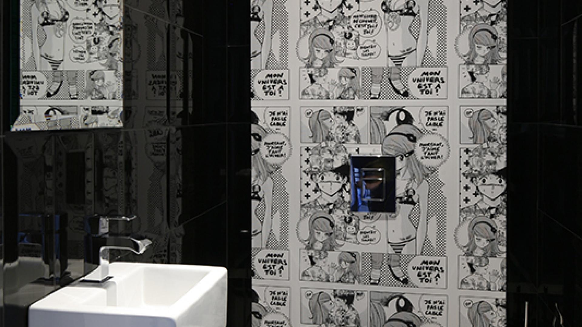 W łazience na parterze komiksowa manga wbrew pozorom świetnie wkomponowała się wczerń płytek zkolekcji Macieja Zienia marki Tubądzin. Wprowadza do łazienki element miłego dla oka zaskoczenia. Fot. Bartosz Jarosz.