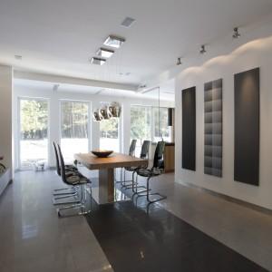 """Ścianę w strefie jadalni zdobią cztery pionowe panele dekoracyjne. Identyczne formaty wybrano celowo; potęguje to ład i harmonię. Różne wzory wprowadzają trochę artystycznego zamieszania. Nad stołem - lampy Oty Light, seria """"Sophie"""". Fot. Bartosz Jarosz."""