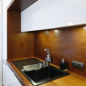 Szafki umieszczone w środkowej części zabudowy wyróżniają się mniejszą głębokością, dlatego nie zawadzają podczas kuchennych prac, a jednocześnie stanowią praktyczny schowek na drobne naczynia, np. szklanki.  Fot. Bartosz Jarosz.