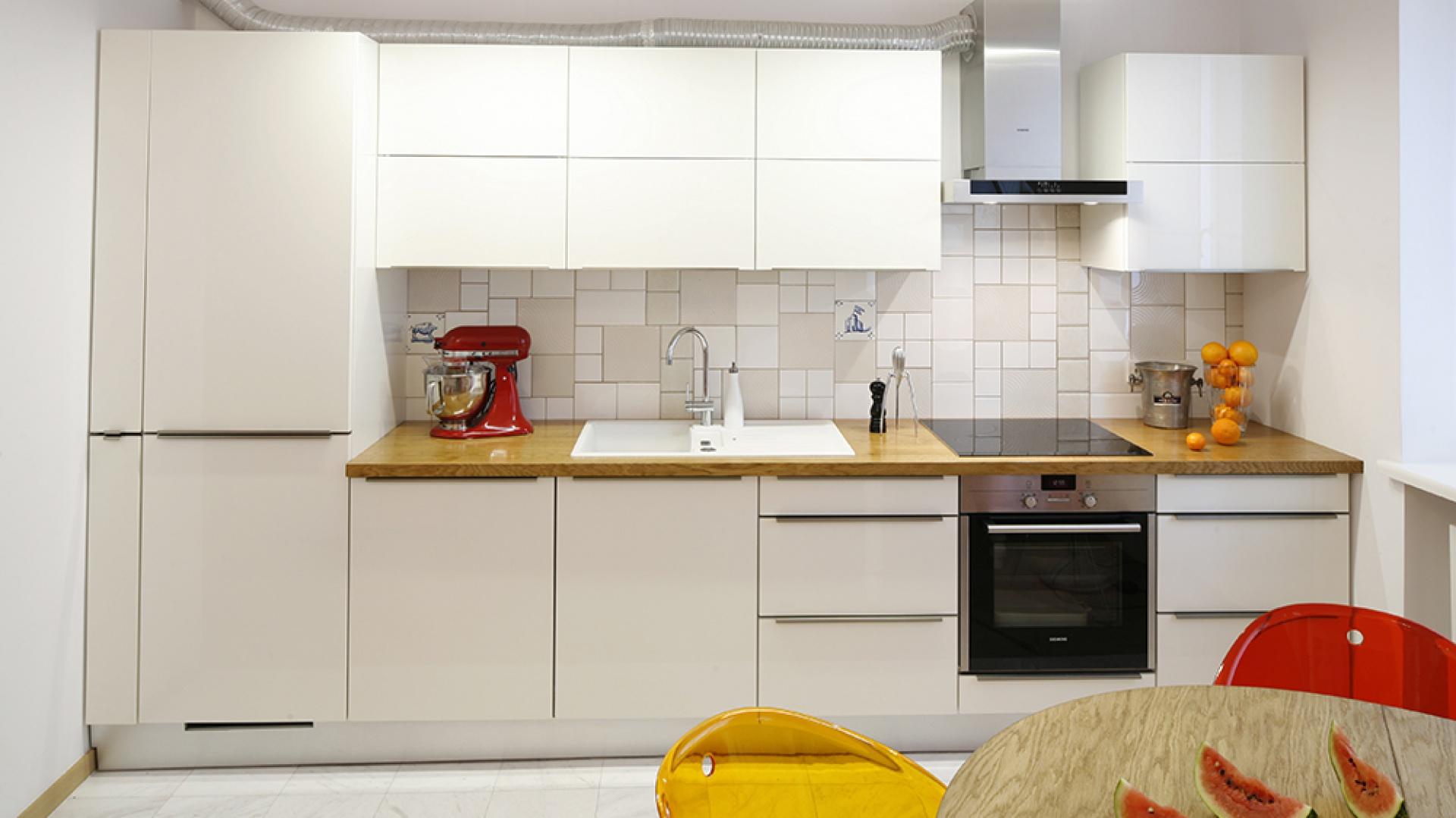 Czystą biel mebli kuchennych przełamuje drewniany blat oraz kaflowe fantazje, układane o 5 rano (!) przez właścicielkę i projektantkę. Fot. Bartosz Jarosz.