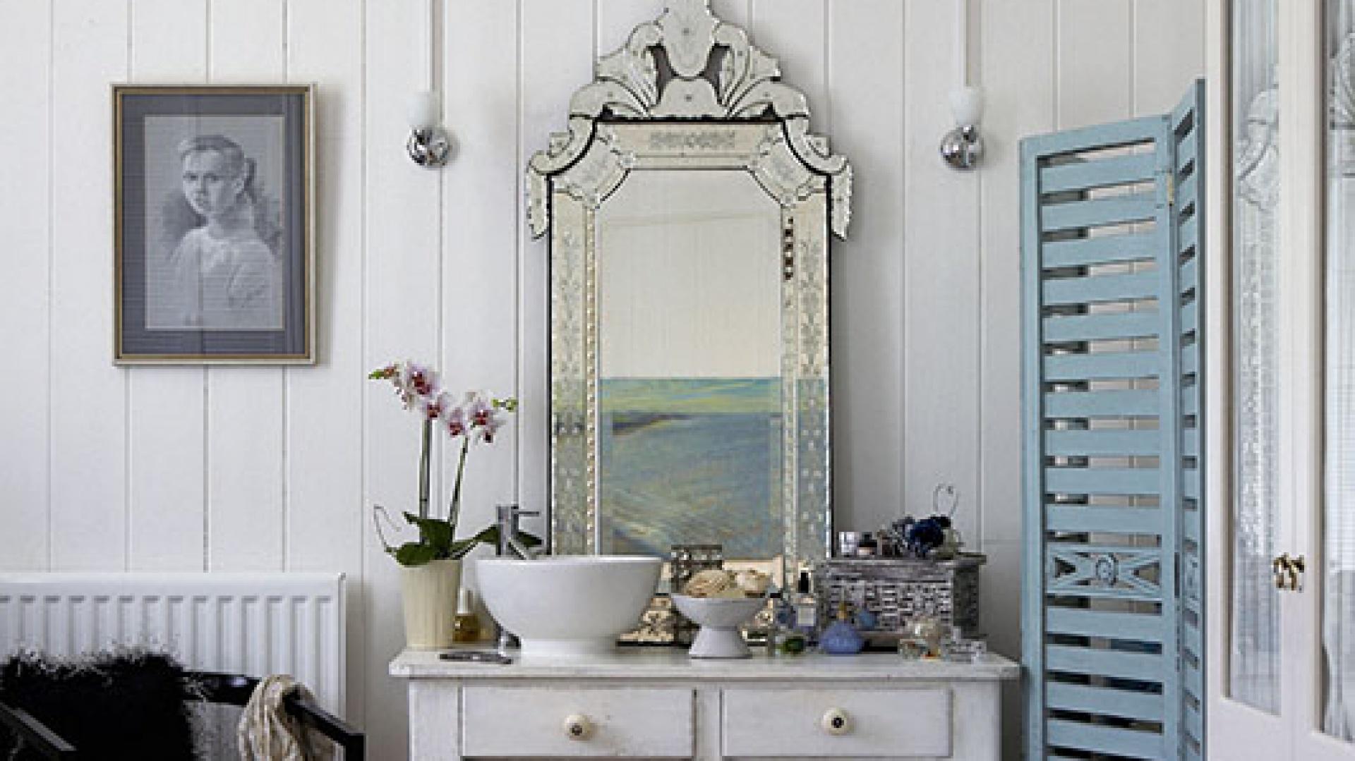 Sypialniana toaletka powstała ze starego kuchennego stołu, który właścicielka odnowiła, pomalowała na biało i skompletowała do niego nablatową umywalkę. Lustro w stylu weneckim i żyrandol w klimacie glamour dopełniają całości. Fot. Brent Darby/Narratives.