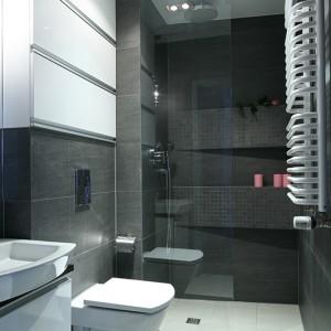 Prysznic z zamontowaną szklaną taflą to pomysł praktyczny i nie ograniczający przestrzeni. Skos ściany prysznicowej aranżatorka wykorzystała projektując masywne półko-wnęki na podręczne kosmetyki. Fot. Bartosz Jarosz.