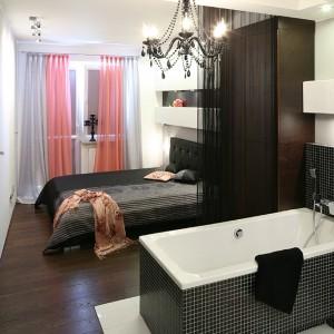 """Stora w postaci zwiewnego czarnego """"spaghetti"""" umownie dzieli pokój na dwie części: w głębi sypialnia, od wejścia pokój kąpielowy. Fot. Bartosz Jarosz."""