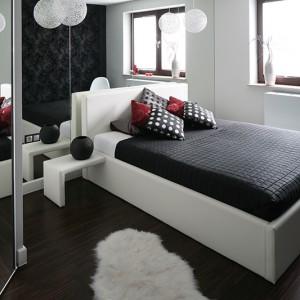 Urzekająca aranżacja kolorystyczna sypialni w czarno-białym duecie. Lustrzana ściana za zagłówkiem łóżka podwaja przestrzeń - jest lekko i przestronnie, mimo czarnej tapety i buduarowego charakteru sypialni. Fot. Bartosz Jarosz.