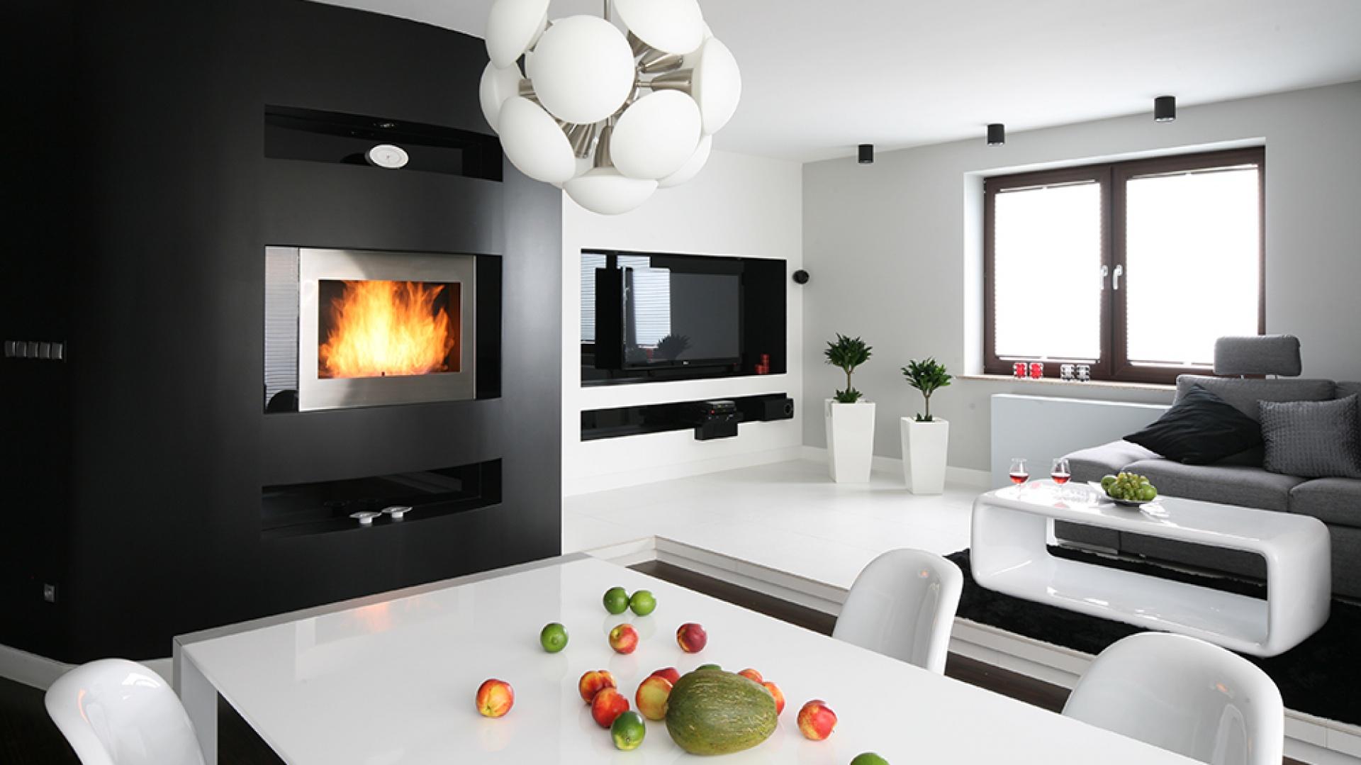 Biel sprawia, że przestrzeń salonu wydaje się większa i przestronniejsza niż w rzeczywistości. Czarna ściana jest tu silną przeciwwagą - to niesłychanie trudne połączenie wymagało zachowania umiaru i równowagi między relacją obu kolorów. Fot. Bartosz Jarosz.