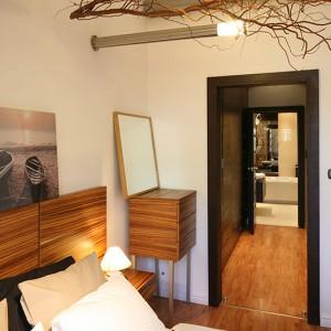 Niebanalne oświetlenie w postaci wyłaniających się ze ściany pod kątem prostym nowoczesnych lamp, skontrastowano w sypialni z nawiązującymi do natury gałęziami wierzby mandżurskiej. Fot. Bartosz Jarosz.