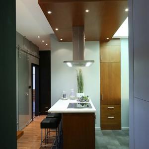 """Drewniany sufit podwieszany to prawdziwa ozdoba kuchni, a zamontowane w nim oświetlenie nie tylko oświetla strefę roboczą, ale zapewnia też atrakcyjną grę świateł. Okap wyspowy Falmec """"Lumen Isola 90"""". Fot. Bartosz Jarosz."""