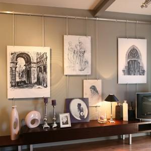 Szarość ścian kontrastuje z rysunkiem drewna zastosowanym w panelach podłogowych. Nowoczesne formy mebli podkreślają elegancki charakter apartamentu. Fot. Bartosz Jarosz.