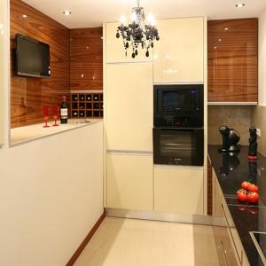 Kuchnię wydzielono z garażu. W efekcie postała  wnęka w ścianie, którą można z powodzeniem wykorzystać np. jako bufet podczas przyjęcia. W głębi – otwarte póki na wino doskonale wykorzystują trudno dostępną przestrzeń. Fot. Bartosz Jarosz.