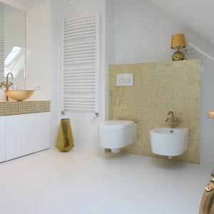 W łazience minimalistyczny chłód bieli przełamuje złota mozaika oraz umywalki i armatura w kolorze złotym. Idealne proporcje bieli i złota gwarantują elegancki charakter wnętrza. Fot. Bartosz Jarosz.