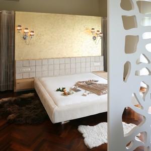 Główną ozdobą tej imponującej sypialni jest wykończona złotymi płatkami ściana za wezgłowiem łóżka. Fot. Bartosz Jarosz.