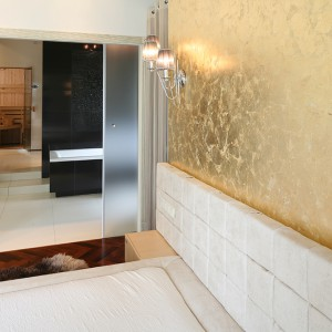 Łazienka sąsiaduje bezpośrednio z sypialnią. Pomieszczenia dzielą jedynie podwójne szklane drzwi. Ściana na łóżkiem wykończona szlagmetalem (złoto płatkowe). Kinkiety wykonała firma Amplex. Fot. Bartosz Jarosz.