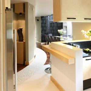 Obszar poszczególnych stref wyznaczają m.in. różne materiały podłogowe: w kuchni polerowany gres (120x60 cm), wokół baru – mozaika kamienna typu palladino, dalej – drewniany parkiet (jesion wędzony). Fot. Bartosz Jarosz.