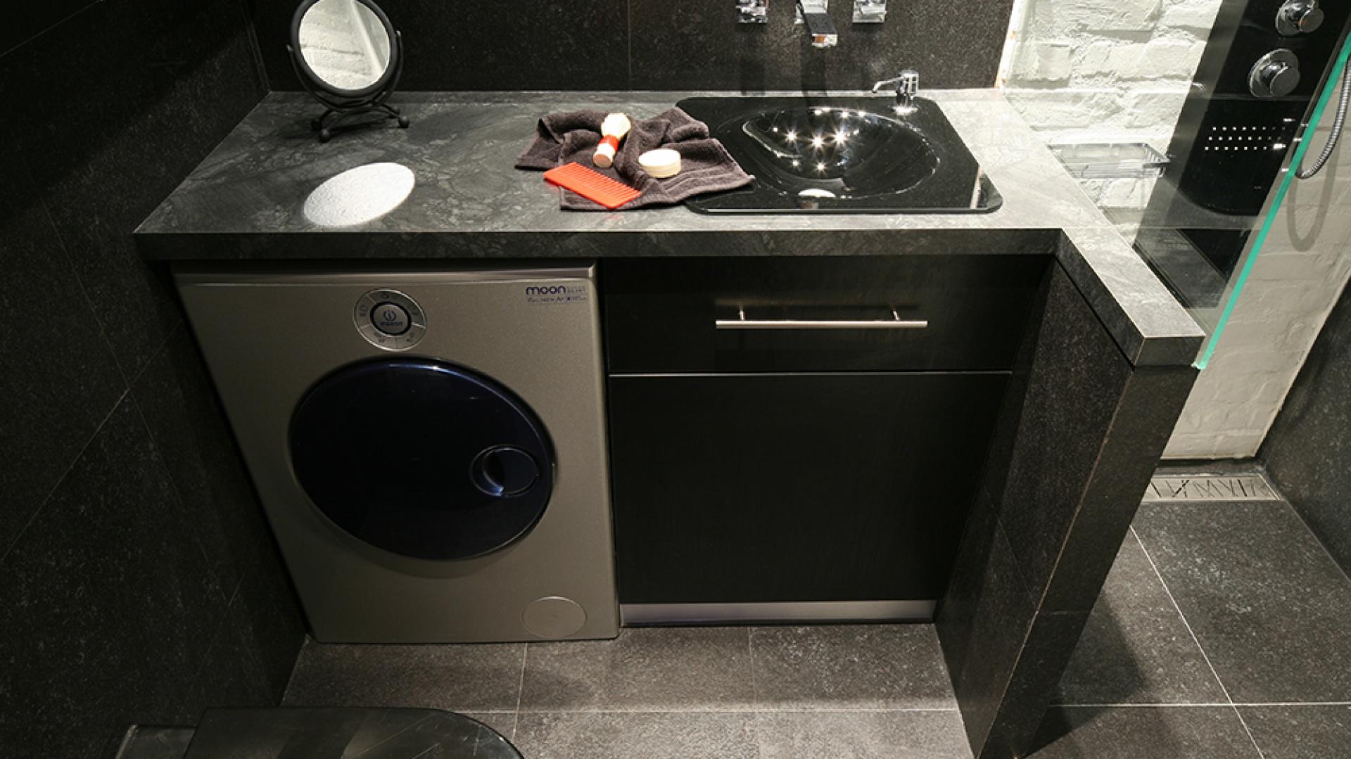 """Stworzona specjalnie do tego wnętrza konstrukcja blatu i szafki podumywalkowej zamyka także częściowo wnękę prysznicową. Pod blatem (z płyty laminowanej) szafka oraz pralka z designerskiej kolekcji """"Moon"""" marki Indesit. Fot. Bartosz Jarosz."""