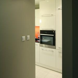 Wszystkie fronty szafek wykonane zostały z białego, lakierowanego MDF-u. Zabudowę kuchenną otwierają dwa wysokie słupki: z piekarnikiem (Küppersbusch) i lodówką (AEG). Fot. Bartosz Jarosz.