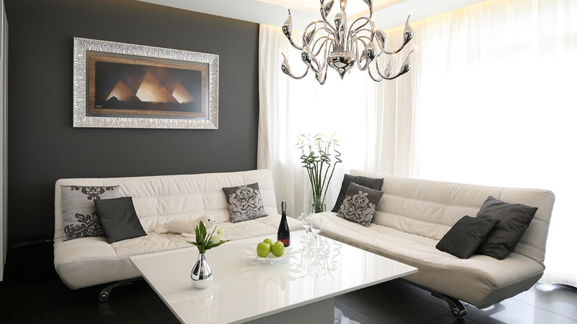 Spowity czernią salon magnetyzuje swą urodą. W tym kolorze jest zarówno tapeta na ścianie, jak i płytki na podłodze. Fot. Bartosz Jarosz.