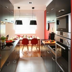 Kuchnia jest przechodnia. Wspólnie z jadalnią tworzy płynnie przenikającą się przestrzeń. Czarny kolor mebli elegancko i apetycznie łączy z kolorami jak na kostce Rubika. Fot. Bartosz Jarosz.