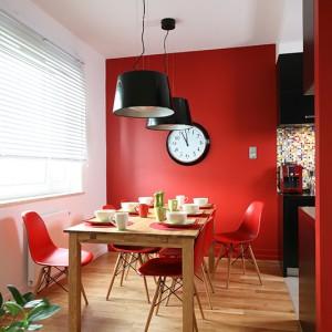 Do dużego, dębowego stołu w jasnym, ciepłym kolorze drewna dobrano delikatne krzesła w żywym, czerwonym kolorze. Fot. Bartosz Jarosz.