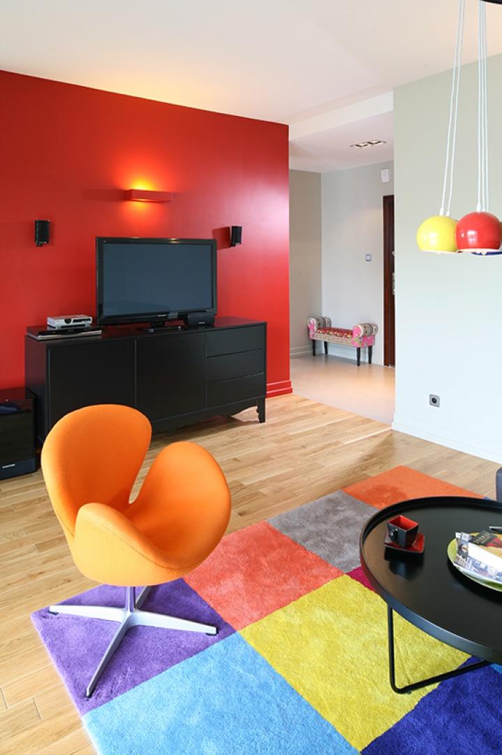 Wygodny, designerski fotel Swan (proj. Arne Jacobsen, w obiciu z wełny) w soczystym, wręcz smakowitym kolorze pomarańczy, doskonale pasuje do całej reszty. Fot. Bartosz Jarosz.