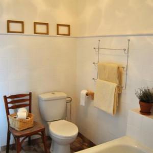 """11-ja-nowa-milnova. """"Łazienka wyremontowana małym kosztem. Wyglądała wczesniej tak http://ja-nowa-milnova.blogspot.com/2010/08/a-azienka.html (pomalowaliśmy kafelki - tak, tak!, wanna została stara), pomimo to jest jasna i przestronna. Uwielbiamy surowe drewno - nie brakuje go też w łazience - szafka pod umywalką i szafka z gałkami w grochy, które sama zrobiłam""""."""