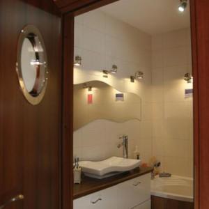"""18-waan. """"Łazienkowa fala, bo motywem przewodnim łazienki jest woda i dlatego wiele elementów przypomina kształtem wodną falę: specjalnie wycięte lustro, umywalka, uchwyty szafki i wzór na płytkach ściennych, a drzwi łazienki zdobi prawie statkowy bulaj""""."""