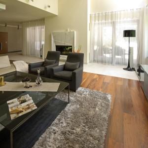 Świetnie odnalazły się tu fotele i kanapa marki Minotti, kominek z marmuru Statuario Extra oraz szklany stolik pomysłu architekta. Fot. Przemysław Andruk.
