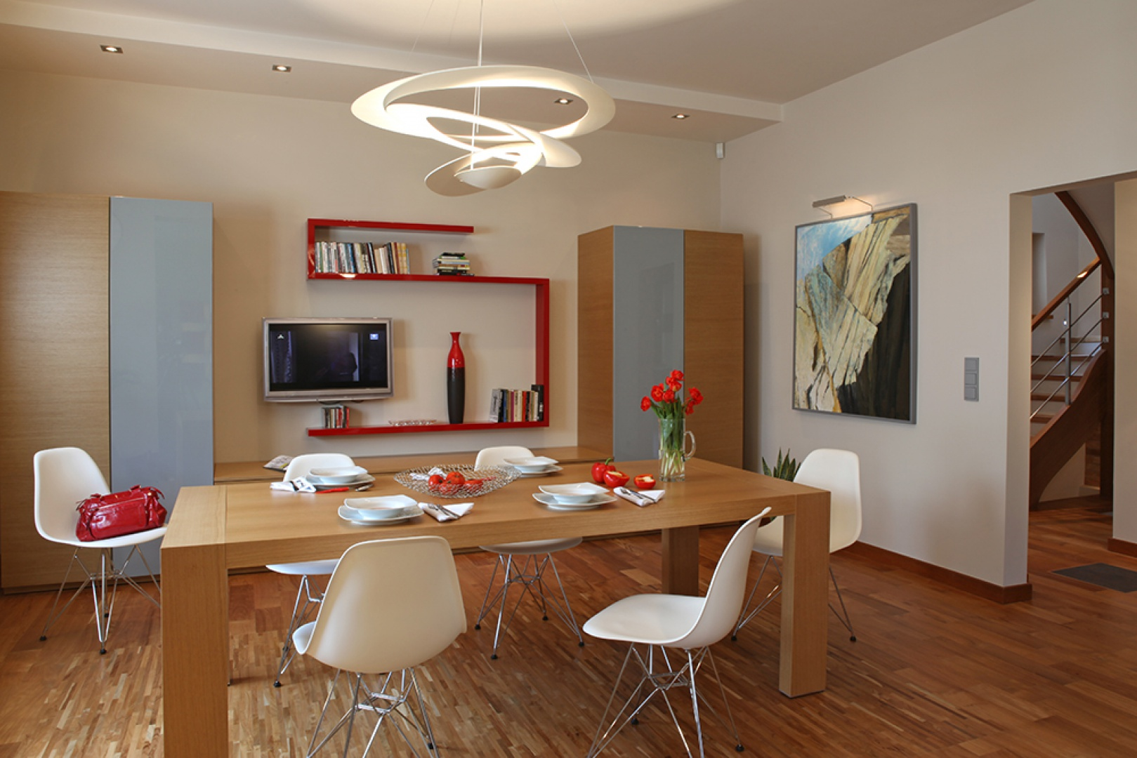 """Jadalnię, tak jak kuchnię, tworzą proste bryły mebli, których forma nawiązuje do modernizmu; fornir dębowy zestawiono z szarym lakierem, symetria oraz czerwone akcenty podkreślają elegancki charakter aranżacji. Zabudowa wykonana na zamówienie; stół Noti """"Compli"""", krzesła Vitra, lampa Artemide """"Price"""". Fot. Monika Filipiuk-Obałek."""
