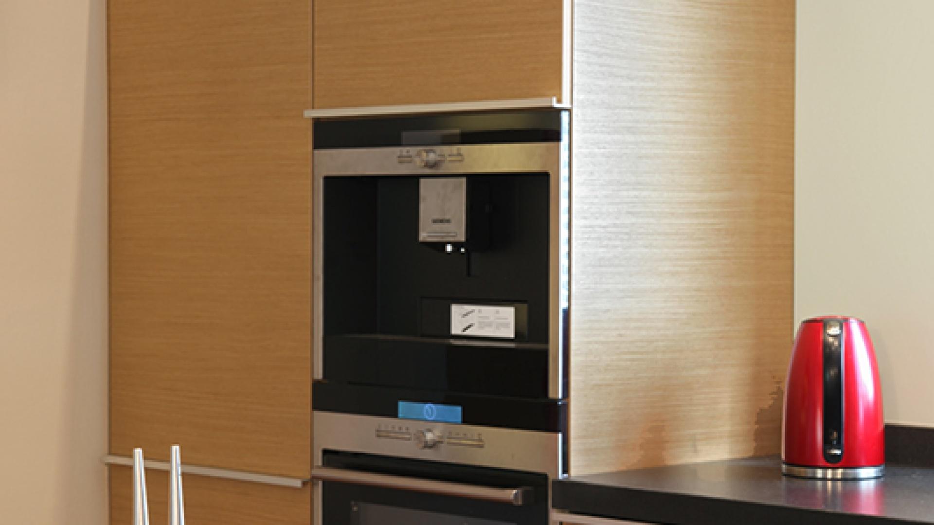 Zabudowa, wykończona modyfikowanym fornirem dębowym, składa się z prostych i lekkich brył. Słupki – nieco niższe od standardowych mieszczą sprzęty AGD: lodówkę (Liebherr), piekarnik, ekspres do kawy (Siemens). Fot. Monika Filipiuk-Obałek.