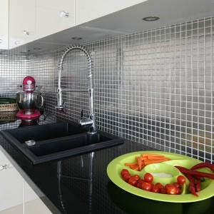 Metalowa mozaika o gładkiej powierzchni w kolorze srebra doskonale komponuje się z ciemnym, granitowym blatem i jasnymi meblami. Jest efektowna i trwała. Fot. Bartosz Jarosz.
