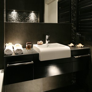 Cała łazienka wykończona jest ciemnym kamieniem. Pokrywa zarówno ściany jak i podłogę. Fot. Bartosz Jarosz.