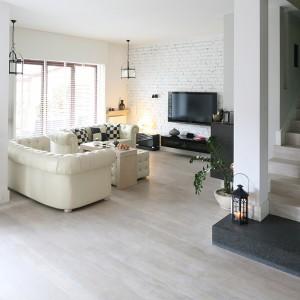 Chłodny klimat salonu ocieplają miękkie, pikowane kanapy (Chesterfield) w kolorze ecru, drewniana podłoga (dąb bielony) i wyrafinowane, glamourowe oświetlenie. Fot. Bartosz Jarosz.