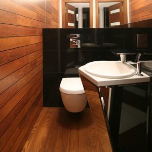 Drewno zastosowane na podłodze oraz jednej ze ścian dodaje surowemu wnętrzu przytulności. Niezwykłą dekoracją toalety jest szafka podumywalkowa wykonana na zamówienie z fazowanego szkła. Fot. Bartosz Jarosz.