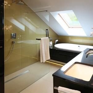 Szklana tafla oddziela prysznic od części z umywalkami, funkcjonalnie dzieląc przestrzeń łazienki. Jest praktycznie niewidoczna, co pozwoliło eksponować szkło lacobel w kolorze złota. Fot. Bartosz Jarosz.