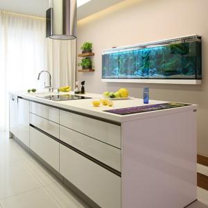 Dominująca w kuchni biel dodaje jej świeżości i lekkości, optycznie powiększa też przestrzeń. Jej wyjątkowy charakter podkreśla duże 300-litrowe akwarium z egzotycznymi rybkami. Ten podwodny świat wzorowany jest na afrykańskim jeziorze Malawi. Fot. Bartosz Jarosz.