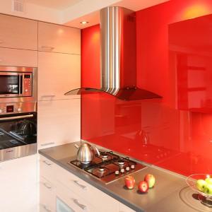 W kolorze czerwonym jest nie tylko ściana, ale i górna zabudowa, dzięki czemu całość sprawia wrażenie jednej, gładkiej powierzchni. Na tym tle świetnie prezentuje się stalowe AGD, m.in. mikrofalówka marki Zelmer oraz piekarnik Bosch. Fot. Bartosz Jarosz.